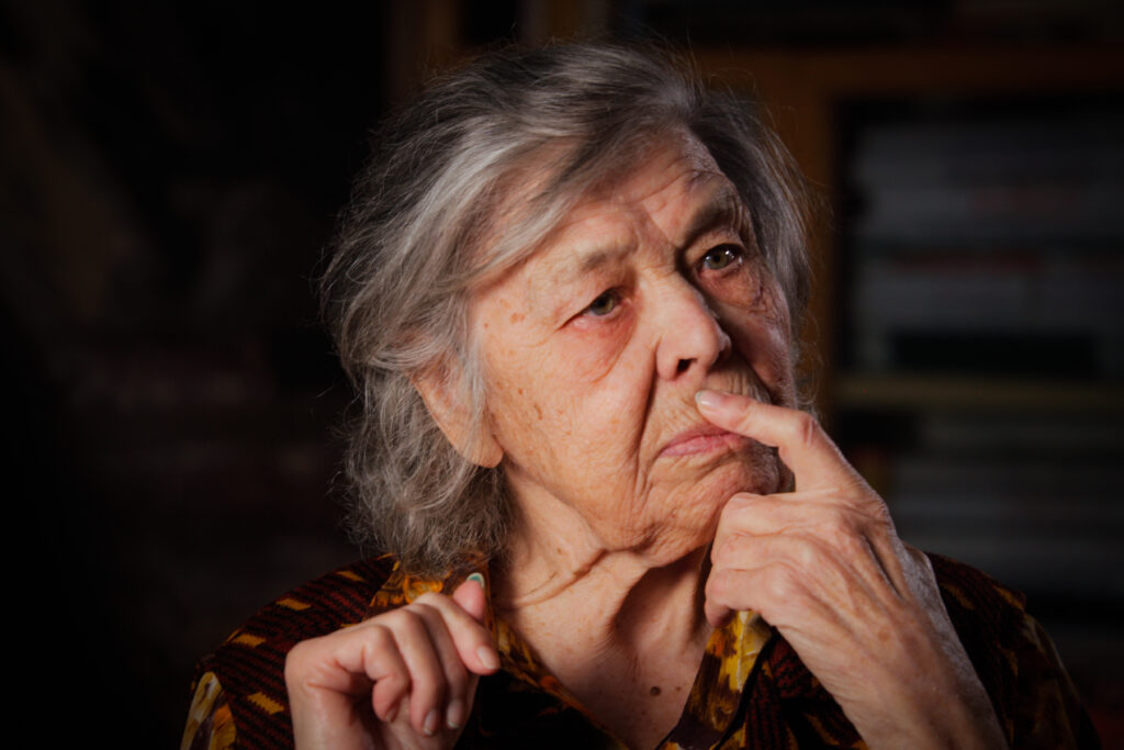 Production still from the film, Women of the Gulag. An elderly woman sits with a finger across her lips